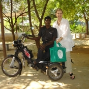 Arumugam with Kathy on the back of his specially adapted bike with their Neem Tree Trust bag