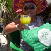 Gillian drinking a tequila on the island of cozumel mexico with her NTT bag